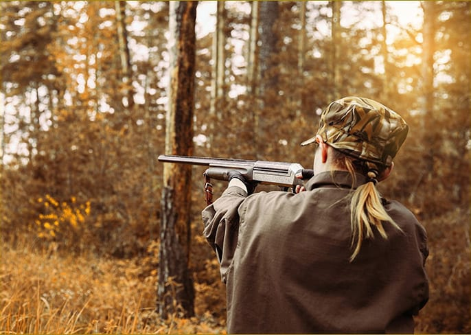 A woman hunting in sunny woods, using hearing plugs