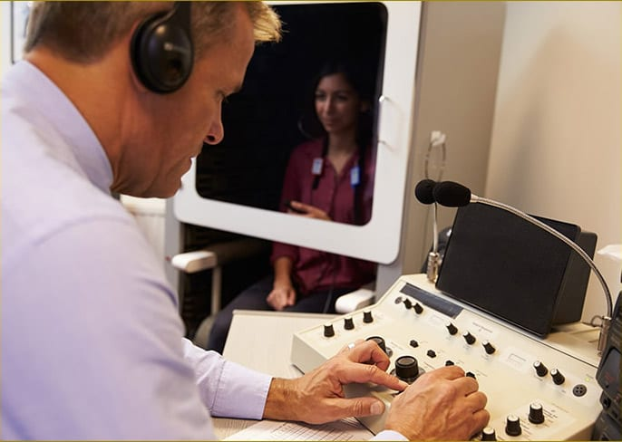 A professional conducting a hearing evaluation