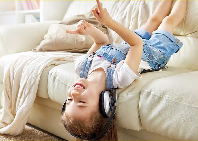 Happy boy upside down on couch, enjoying headphones