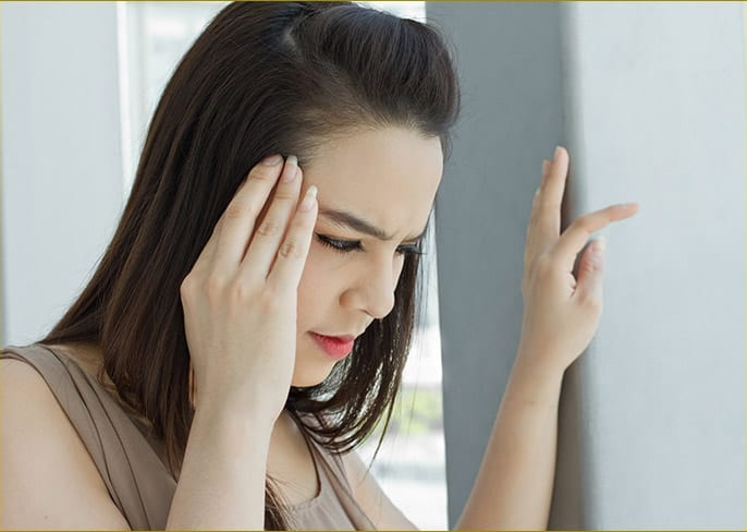 A woman visibly suffering from Tinnitus